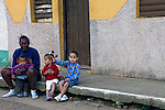 Central America, Cuba, Remedios. Cuban mother sits with her young children on street in Remedios.