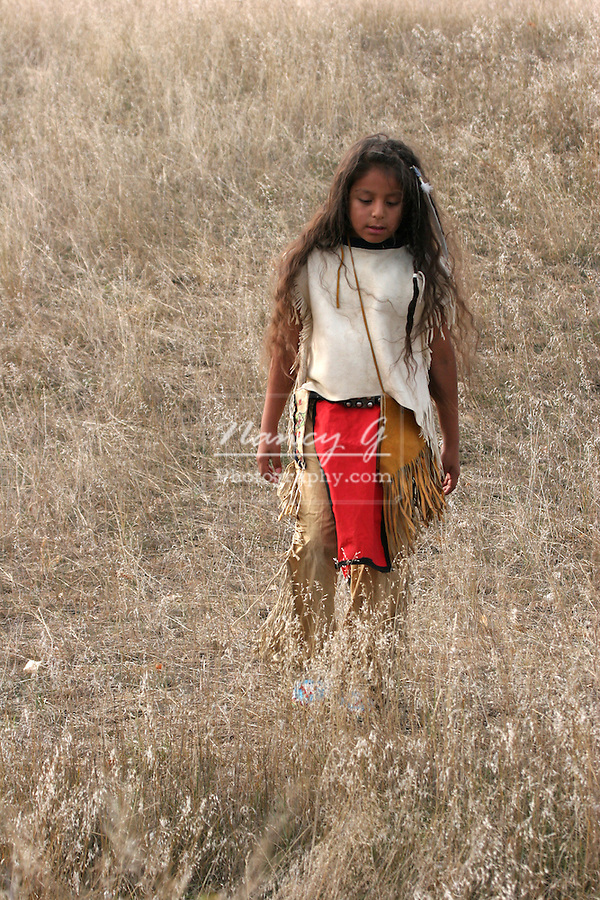 A young Native American Indian boy walking through the long dried grass in the plains of South Dakota