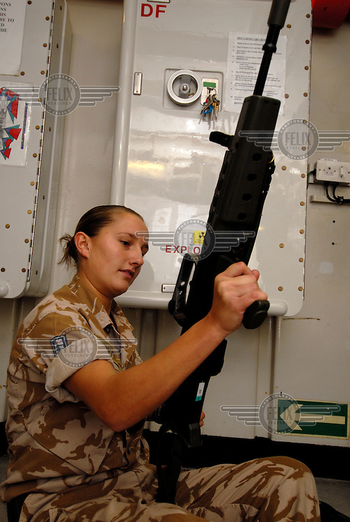 Weapons cleaning aboard HMS Campbeltown. Able Seaman Nadine Kelly is the only woman in the boarding party which searches tankers and fishing boats.