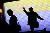 Pedestrians play with a large digital screen which changes colour as you touch it, in the street in Shinjuku district, Tokyo, Japan, on Wednesday, Nov. 22, 2006.