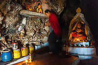 A young scholar of Buddhism inside a sacred cave, preparing the site for a daily prayer and devotional ceremony.