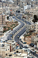 Jordan. Amman.Downtown. Town center. Traffic on a bend road which looks like a s letter. Muslim men and women walk on the pavement.Traditionnal buildings and constructions where are set on most of the roofs watertanks and parabolic aerials to get better reception on television programms. © 2002 Didier Ruef