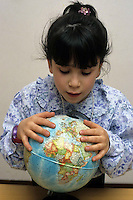 Bambina e mappamondo. Baby-girl and globe....
