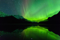 The aurora borealis is reflected in Chilkoot Lake near Haines in Southeast Alaska. Winter. Evening.