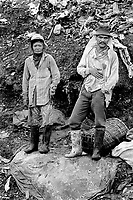 Philippines. Luzon Region. Manila. Tondo area. Smokey mountain is a rubbish dump. Life on a garbage heap. A couple of scavengers on dumpsite. Both man and woman wear plastic boots. They collect various rubbish items in order to resell them as recycled products. © 1992 Didier Ruef ..
