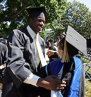 Virginia football player De'Brickshaw Ferguson, left,  receives a hug from faculty member Maria-Ines Lagos during the 2006 gradution ceremonies Sunday May 21, 2006 at the University of Virginia in Charlottesville, Va.