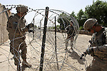 Soldiers with Company B, 2nd Battalion, 508th Parachute Infantry Regiment, string concertina wire around a compound they've taken over for a new outpost in the village of Deh-e- Chowkay, in the Arghandab valley near Kandahar, Afghanistan. May 24, 2010. DREW BROWN/STARS AND STRIPES