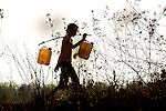 A farm girl carrying home heavy containers of water in Hongsa, Laos.