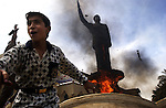 An Iraqi boy cheers as a statue of ousted Iraqi President Saddam Hussein is set ablaze during an impromptu celebration on the streets April 12, 2003 in downtown Baghdad, Iraq.