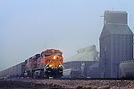 Emerging from a thick blanket of fog at Inland, NE, an eastbound BNSF coal train rolls by the small town grain elevator.