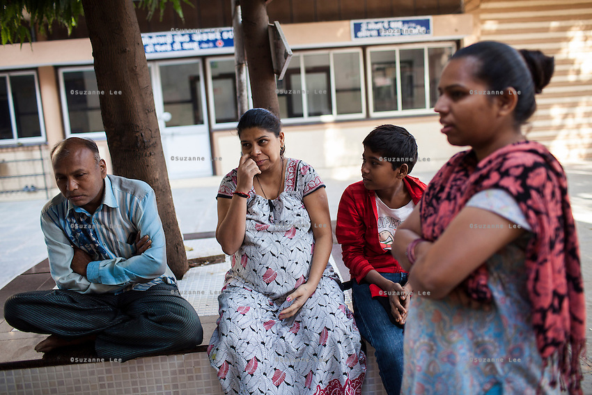Leela Mekwan (center), 34, sits with her husband Jayantibhai (left), 38, and son Ashish (right), 14, as a nurse, Sejal Parmar, 32, looks on in the Akanksha IVF and surrogacy center in Anand, Gujarat, India on 9th December 2012. Leela is 9 months pregnant with her 2nd surrogacy that she is doing with Dr. Nayana Patel and has support from her immediate family including her 2 sons. Photo by Suzanne Lee/Marie-Claire France