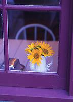 Vase of sunflowers on table looking through window