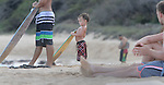 A young boys mirrors the other skim boarders that hangout out on Sandy Beach in Hawaii.
