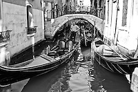 A Venice canal view of Gondolas in black and white.