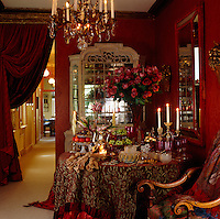 The use of sumptuous textiles such as the velvet curtains and tablecloth add to the drama of this opulent dining room