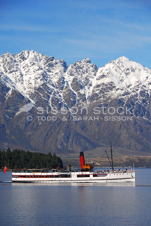 TSS Earnslaw heading to Walter Peak Station. Snow covered Remarkables mountains behind, Queenstown, New Zealand