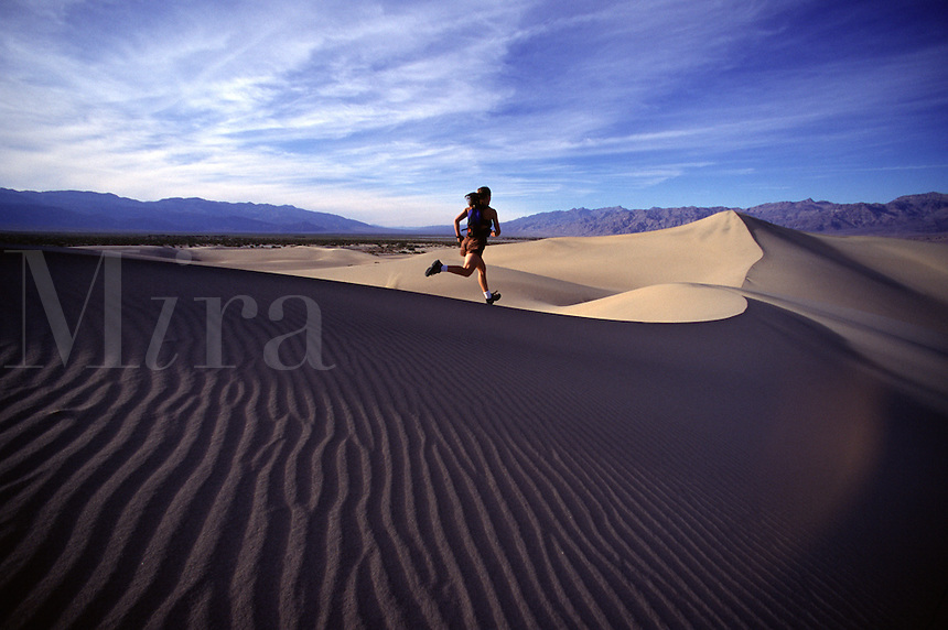 A woman running on a sand dune in Death Valley, CA.