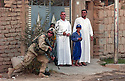 U.S. Army 4th Infantry Division, 1st Battallion, 12th regiment Sergeant Joshua Swanson from St. Joseph, MO moves past an Iraqi family's house during an evening presence patrol through Samarra, Iraq August 24, 2003.