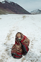 After 5 days, a member of a caravan hides from the frigid wind under a blanket. The Pamir plateau is just half a day away..Trekking through a plain called Mirzo Murad. .Trekking up to the Little Pamir with yak caravan over the frozen Wakhan river.