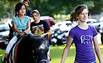 Southbury, CT- 14 June 2015-061415CM03- Sofie Rodriguez, 5, of Oxford rides Megan a pony escorted by Hannah Geraci of Woodbury, during the annual  Southbury Strawberry Festival at the United Church of Christ in Southbury on Sunday.  The event featured homemade strawberry shortcake, chocolate-covered strawberries, barbecued food, activities for children, pony rides, live music and dancing.  Christopher Massa Republican-American