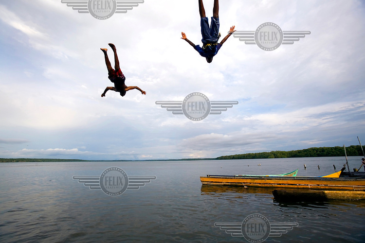 Two boys dive into the ocean off the island of Limones.