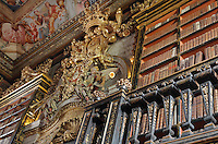 Gilded sculptural crown and angels, exalting the King and Portugal, above a portrait of King John V or Joao V, 1689-1750, by Domenico Dupra, 1725, and bookshelves with Chinese motifs, lacquer and gilding by Manuel da Silva, in the Black Room of the Joanina Library, or Biblioteca Joanina, a Baroque library built 1717-28 by Gaspar Ferreira, part of the University of Coimbra General Library, in Coimbra, Portugal. The Casa da Livraria was built during the reign of King John V or Joao V, and consists of the Green Room, Red Room and Black Room, with 250,000 books dating from the 16th - 18th centuries. The library is part of the Faculty of Law and the University is housed in the buildings of the Royal Palace of Coimbra. The building is classified as a national monument and UNESCO World Heritage Site. Picture by Manuel Cohen