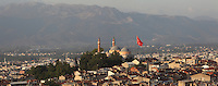 Evening view of the city of Bursa with the Grand Mosque and a Turkish flag and mountains in the distance, Turkey. Bursa is situated in North West Anatolia and is the fourth largest city in Turkey. It became the first major capital city of the early Ottoman Empire following its capture from the Byzantines in 1326 and was the centre of the Turkish silk industry until the 17th century. The Grand Mosque or Ulu Cami is the largest mosque in Bursa and was built 1396-1400. Picture by Manuel Cohen