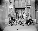 FOOTBALL TEAM AT EVERETT ELEMENTARY SCHOOL. Everett Elementary School was built in 1887 at Eleventh and C Streets. Harrison Johnson built his house two blocks away in 1891 and presumably his son, John, attended school here. The football team John Johnson photographed at the schoolhouse door proudly displays its Everett pennant. Although mixed in age, size, race, and equipment, another damaged negative shows the group lined up in football formation. One youth's striped-sleeve jersey resembles the uniform of the University of Nebraska team in that era. The African American man standing to the left of the pennant may be Pendleton Murray, who graduated from Lincoln High School in 1917 and worked as a carpet cleaner and later as a turnkey at the county jail. Everett Junior High School replaced this school in 1928, then was converted back into an elementary facility in 1990.<br />