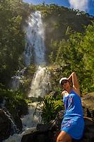 A local woman takes in the sun at the foot of cascading Hi'ilawe Falls (or Hi'ilawe Waterfall), Waipi'o Valley, Big Island.