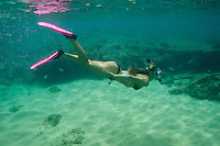 A healthy, fit woman snorkels at Napili Bay, Maui.