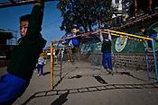 Tibetan Children play on the swings at the Tibetan Children's Village School in Dharamsala in Himachal Pradesh, India. Photo: Sanjit Das/Panos