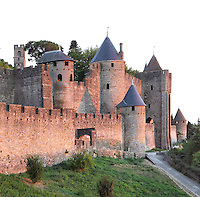 Comtal Castle, seen from the Lower Lists (sloping terrain between the two lines of defences), Citadel of Carcassonne, Aude, France. Carcassonne was a stronghold of Occitan Cathars during the Albigensian Crusades but was captured by Simon de Montfort in 1209. He added extra fortifications and Carcassonne became a citadel on the French border with Aragon. The fortress restored in 1853 by Eugene Viollet-le-Duc. Today it is a UNESCO World Heritage site. Picture by Manuel Cohen
