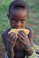 A young Bana eats the bee larvae, called bees' milk. ///Une jeune Bana mange des larves d'abeilles, appelées lait des abeilles.