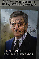 France. Ile de France. Paris. Partially torn campaign poster of French presidential election candidate François Fillon for the right wing Les Républicains (LR). A graffiti with ta chewing gun on his nose and written words: Crook, thief, you are dead. 21.04.17  © 2017 Didier Ruef