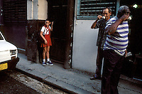 Cuban workers stop for a shot of coffee at a street-side stand while a young student heads off for a day at school in Habana Vieja, or Old Havana.