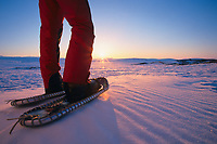 The winter sun sets as a snowshoer pauses while recreating in the Brooks mountain range, arctic, Alaska