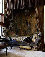 In the guest bedroom, velvet curtains enclose a Russian sleigh bed and the back wall is covered with an Aubusson tapestry