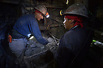 Two miners load ore in a cart deep under Cerro Rico in Potosi, Bolivia. The mine produces silver and other metals.