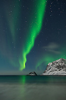 Aurora Borealis - Northern Lights shine in sky over snow covered mountains from Vik beach, Vestvågøy, Lofoten Islands, Norway