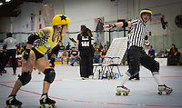 "Jammer referee Override signals ""not lead jammer"" white skating alongside Bump'Er Car, the jammer for the Crash Test Bunnies.  Portions of this image not central to the content have been digitally altered."