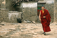 A monk walks the narrow streets near the Mindroling Monastery. The Mindroling Monastery was founded in 1676 by Rigzin Terdak Lingpa, and is one of the six major monasteries of the Nyingma school in Tibet..