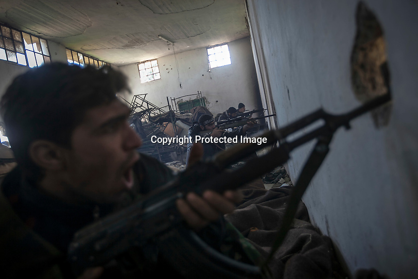 In this Saturday, Dec. 15, 2012 photo, a Syrian rebel fighter encourages his comerades shouting Muslim hymns as they aim toward government forces during heavy clashes inside one militar academy besieged by rebels at the north of Aleppo, Syria. The Free Syrian Army took control over the Academy after several hours battling the troops loyal to President Bashar al-Assad. Among the casualities are one FSA General and one Syrian journalist. (AP Photo/Narciso Contreras)