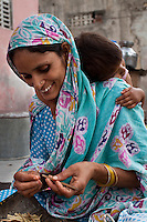 Nafeesa, 27, rolls bidis (indian cigarettes) as her youngest of 4 children aged 10, 7, 4, and 1.5 years, hangs on to her in her house compound in a slum in Tonk, Rajasthan, India, on 19th June 2012. Nafeesa's health deteriorated from bad birth spacing and over-working. While her husband works far from home, she rolls bidis (indian cigarettes) to make an income and support the family. She single-handedly runs the household and this has taken a toll on her health and financial insufficiencies has affected her children's health. Photo by Suzanne Lee for Save The Children UK