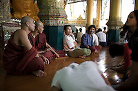 A group of university students meet with monks at the Shwedagon Pagoda.
