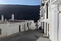 Streets and houses with mountainous background, Capileira, Poqueira gorge, Alpujarra, Andalucia, Southern Spain. Moorish influence is seen in the distinctive cubic architecture of the Sierra Nevada's Alpujarra region, reminiscent of Berber architecture in Morocco's Atlas Mountains. Photograph by Manuel Cohen.