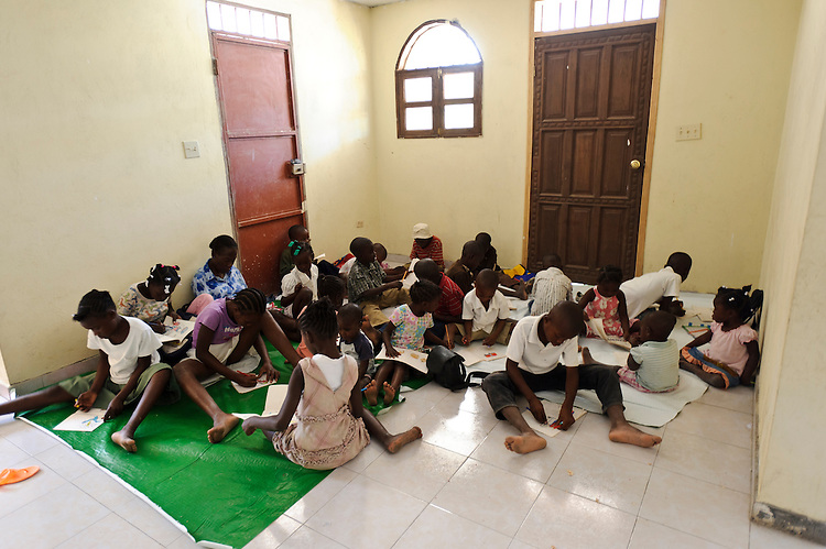 Young children studying in the existing classroom at an orphanage supported by EDV, Port-au-Prince, Haiti. EDV is committed to affecting permanent change in disaster-affected communities worldwide. Their role is to facilitate personal connections between volunteers and the survivors of disasters.  The charity is based on a proven model developed by several landmark organisations that have paved the way for citizens to become disaster volunteers. These landmark organisations have shown that supposedly ordinary people working together with the guidance of knowledgeable leaders can make an extraordinary difference in the lives of those affected by disaster..EDV believe that to provide meaningful relief and reconstruction assistance to disaster affected communities they have to do more than reconstruct buildings. They need to understand and address the factors that made a community vulnerable to the disaster in the first place. The charity's work is organised with these factors in mind so that they can affect change that far outlives their presence..EDV believes that survivor motivation is essential to the recovery of any disaster-affected community. Their operations will always be predicated on the idea that survivors may be traumatised, but they are not helpless. With this in mind, EDV encourages host communities to direct their own recovery. EDV believe that this empowerment is essential in helping survivors feel a renewed sense of control over their lives which will, in turn, help overcome the feelings of hopelessness that can follow a disaster and inhibit long term recovery. EDV also believe that social cohesion is of primary importance in any disaster-affected area. No amount of bricks or mortar will bring about sustainable improvement if communities fail to come together or are disrupted by relief efforts. Therefore, their operations will always aim to foster communication and cooperation within and between the communities they serve.