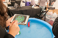 "Visitors to the NYU-Polytechnic School of Engineering,s second annual Research Expo in Brooklyn's ""Tech Triangle"" in New York on Friday, May 2, 2014 operate Raymond LeGrand and Paul Phamduy's robotic fish. LeGrand, a Masters student, developed the app and Phamduy, a Phd student, built the mechanical fish. They worked on their project for a year. Over forty research projects and their creators will exhibit and explain their research including cutting-edge robotics, engineering and biotechnology.  (© Richard B. Levine)"