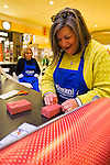 Dec. 12, 2012 - Garden City, New York, U.S. - LINDA SUSMAN, of Merrick, a member of the Merrick Kiwanis Club, a community service group, gift wraps presents at Roosevelt Field mall in Long Island to help raise funds to use for charity, during the busy winter holiday shopping season. She and CAROLE METZGER of Plainview, behind her, were among members of Meadowbrook Women's Initiative helping at the booth. Some ways Kiwanis helps the community are by providing food, clothing, and school supplies to those in need, sending children to Kamp Kiwanis, providing scholarships and hosting a Harvest Ball for senior citizens.