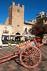 Traditional Sicilian cart infront of the gate tower on  on the Plaza ix Aprile with trees in blossom - Taormina, Sicily