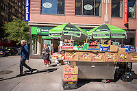 A fruit and vegetable stand in the Upper West Side neighborhood of New York with umbrellas advertising TD Bank, in front of a TD Bank on Sunday, October 20, 2013.  (© Richard B. Levine)